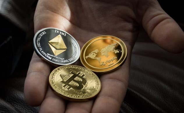 Hand holding ethereum and bitcoin cryptocurrency coins