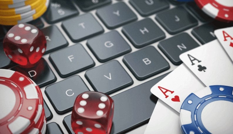 Casino chips and red dice over a computer keyboard